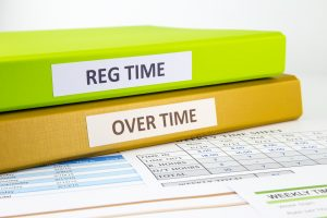 Regular time and Over time words on labels, document binders place on employee time sheets