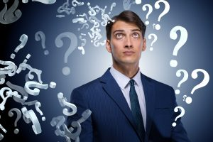 Businessman in uncertainty concept with many unanswered questions