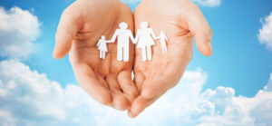 people, values and happiness concept - close up of man cupped hands showing paper family cutout over blue sky and clouds background